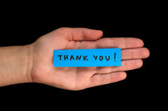 Frase Thank You on paper and hand Stock Image