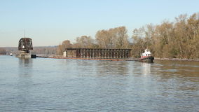 Fraser River Tugboat and Logboom. An old, swing span, rail bridge over the Fraser River is open to allow a tugboat and log boom to travel up river. British stock footage