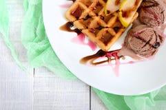 Frasig belgisk dillande med stycken av päronet, bär- och chokladsirap och glassbollar Royaltyfri Fotografi