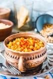 Frasiga bakade kikärtar med kryddor på lantlig bakgrund Royaltyfri Bild