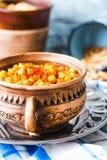 Frasiga bakade kikärtar med kryddor på lantlig bakgrund, selectiv Royaltyfri Bild