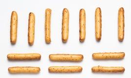 Frasiga breadsticks med vallmofrön som ordnas i rader på en vit bakgrund royaltyfria foton