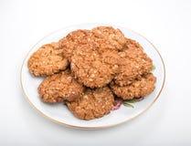 Frasiga havrekex/kakor på en vit platta med den guld- kanten Arkivfoton