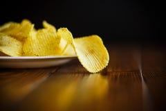 Frasiga potatischiper i en vit platta Arkivfoto