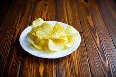 Frasiga potatischiper i en vit platta Arkivbild