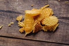 Frasiga potatischiper p? tr?bakgrund chiper startade royaltyfri bild