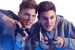 Fratelli adolescenti che giocano i video giochi divertenti immagini stock