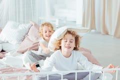 Fratelli che hanno lotta di cuscino di mattina Immagine Stock