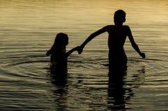 Fratelli che si tengono per mano nell'acqua di un lago al tramonto Immagini Stock Libere da Diritti