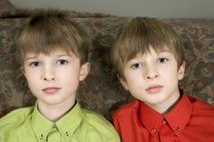 Fratelli di gemelli che si siedono insieme fotografia stock