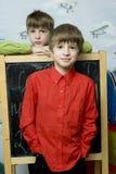 Fratelli di gemelli felici che si levano in piedi alla parete. immagini stock libere da diritti