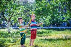 Fratelli divertendosi spruzzata con acqua nel villaggio fotografie stock