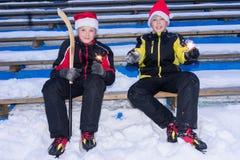 Fratelli gemelli che tengono i bastoni del Bengala sulla pista di pattinaggio sul ghiaccio fotografia stock libera da diritti
