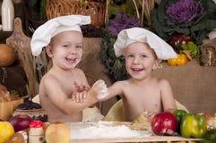 Fratelli germani che cucinano in cappelli del cuoco unico Fotografie Stock