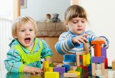 Fratelli germani che giocano con i giocattoli di legno Fotografia Stock