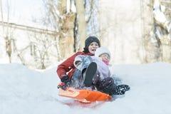 Fratelli germani che hanno divertimento in discesa sul cursore di plastica della neve di inverno all'aperto Fotografie Stock Libere da Diritti