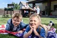 Fratelli germani che riposano sulla bandiera americana con la famiglia che ha picnic dietro Fotografia Stock Libera da Diritti