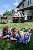 Fratelli germani che riposano sulla bandiera americana con la famiglia che ha picnic dietro Fotografie Stock Libere da Diritti