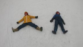Fratelli germani che si trovano sulla neve e sul braccio di uso per l'ala e volare archivi video