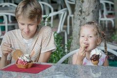 Fratelli germani della ragazza e del ragazzo che godono del loro gelato italiano in gelateria fotografie stock