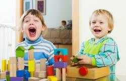 Fratelli germani emozionali con i blocchetti del giocattolo nella casa Fotografia Stock