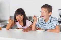 Fratelli germani felici che mangiano cereale per la prima colazione in cucina fotografie stock