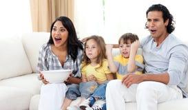 Fratelli germani svegli che guardano TV con i loro genitori Fotografie Stock