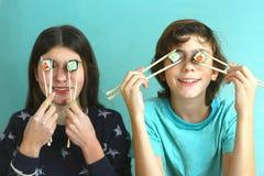 Fratelli germani teenager ragazzo e bambini della ragazza con i rotoli di sushi Fotografia Stock