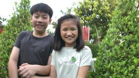 Fratello asiatico e sorella che vanno in giro nel parco e che ridono insieme, archivi video