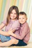 Fratello che abbraccia sua sorella più anziana che si siede su un pavimento Fotografia Stock