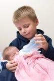 Fratello che alimenta la sua sorella. fotografia stock