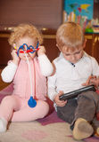 Fratello con la compressa digitale, sorella con il corredo medico del giocattolo Immagini Stock Libere da Diritti
