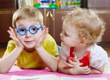 Fratello divertente in vetri del giocattolo con la sorella sul pavimento Immagini Stock