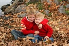 Fratello e sorella che abbracciano alla sosta Immagini Stock