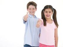 Fratello e sorella che danno i pollici in su che sorridono Fotografie Stock