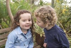 Fratello e sorella che dividono un segreto Immagini Stock
