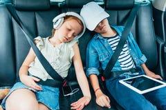 fratello e sorella che dormono sui sedili posteriori dell'automobile mentre fotografie stock libere da diritti