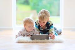 Fratello e sorella che giocano con il pc della compressa Fotografia Stock