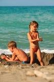 Fratello e sorella che giocano dopo la nuotata alla spiaggia Fotografia Stock