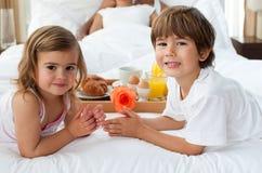 Fratello e sorella che mangiano prima colazione con il loro Immagini Stock Libere da Diritti