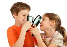 Fratello e sorella che osservano tramite le lenti di ingrandimento Fotografie Stock