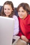 Fratello e sorella che per mezzo di un computer portatile Immagini Stock