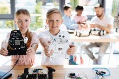 Fratello e sorella che posano con i modelli del robot Fotografia Stock