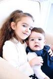 Fratello e sorella che si siedono all'interno sorridere ed abbracciare Immagini Stock Libere da Diritti