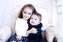 Fratello e sorella che si siedono all'interno sorridere ed abbracciare Fotografia Stock Libera da Diritti