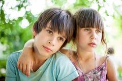Fratello e sorella che si siedono su un banco nel villaggio Fotografia Stock