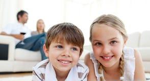Fratello e sorella che si trovano sul pavimento Fotografie Stock
