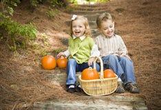 Fratello e sorella di risata Children Sitting sui punti di legno con le zucche Fotografie Stock Libere da Diritti