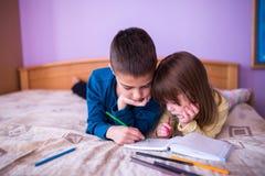 Fratello e sorella disegno di Having Fun al letto Fotografie Stock