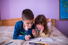 Fratello e sorella disegno di Having Fun al letto Fotografie Stock Libere da Diritti